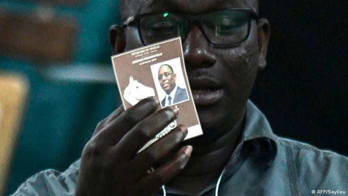Ein Wahlhelfer mit einem Wahlzettel, der Macky Sall zeigt