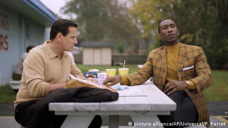 Film Green Book - Szene mit einem schwarzen und einem weißen Darsteller bei einer Picknick-Pause draußen an einem Holztisch (picture alliance/AP/Universal/P. Perret)