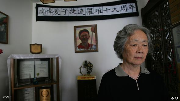 Ding Zilin, co-founder of the Tiananmen Mothers, a group representing families of those who died in the 1989 crackdown on pro-democracy demonstrations, stands in front of a shrine to her son, Jiang Jielian, at her apartment in Beijing Wednesday June 4, 2008. Wednesday is the 19th anniversary of the military assault in which hundreds, possibly thousands, were killed as Chinese troops shot their way through the city to end weeks of protests in Tiananmen Square. (AP Photo/Greg Baker)