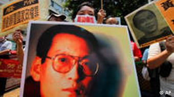Activists hold pictures of Liu Xiaobo during a protest outside the Chinese government's liaison office in Hong Kong