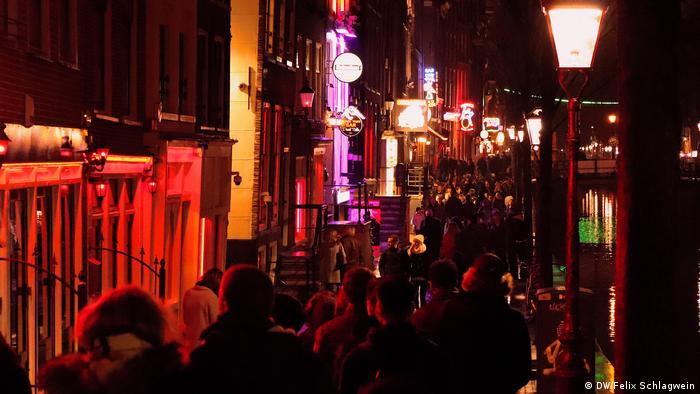 At night many tourists walk through the reddish glow of the streets in Amsterdam's red-light district