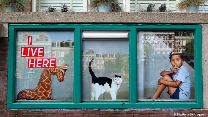 In three windows a stuffed giraffe, a cat and a boy holding a finger in front of his mouth stand next to each other. The text reads I live here.