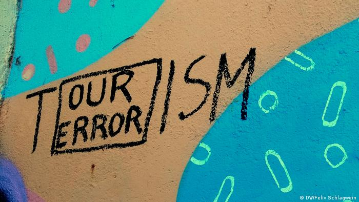 On a wall in Lisbon an inscription equates tourism with terrorism (DW/Felix Schlagwein)