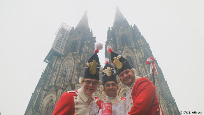 Three Rote Funken standing in front of the Cologne cathedral (DW/S. Wünsch)