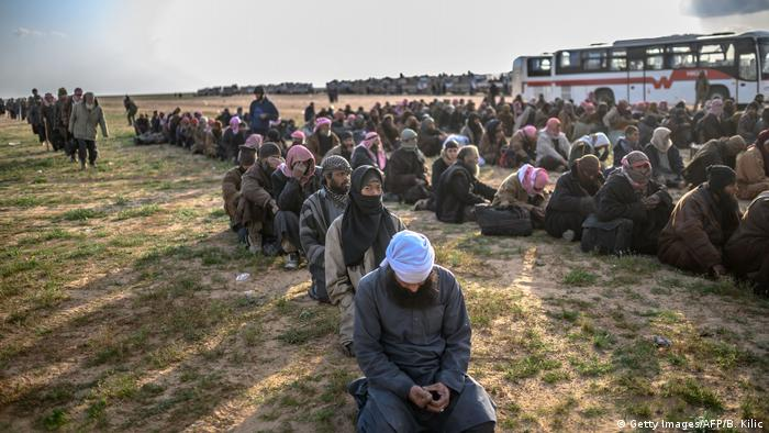 Men suspected of being Islamic State (IS) fighters wait to be searched by members of the Kurdish-led Syrian Democratic Forces (SDF) after leaving the IS group's last holdout of Baghouz, in Syria's northern Deir Ezzor province on February 22, 2019