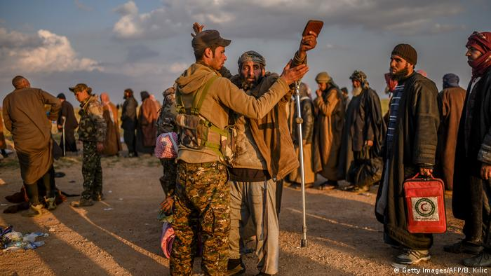 Men suspected of being IS fighters are searched by the Kurdish-led SDF after leaving the last holdout of Baghouz in Syria's northern province