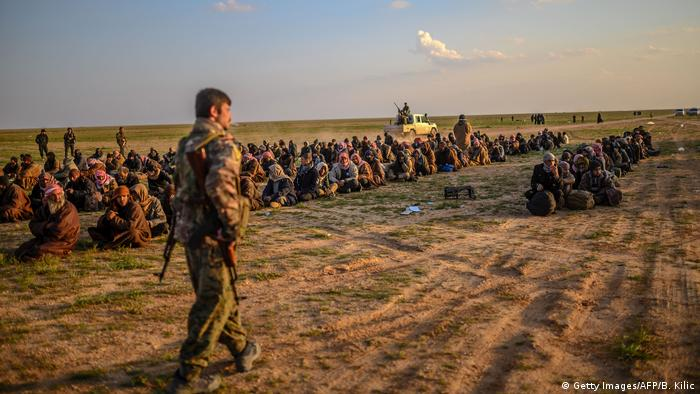 Men wait to be searched after leaving the IS holdout of Baghouz