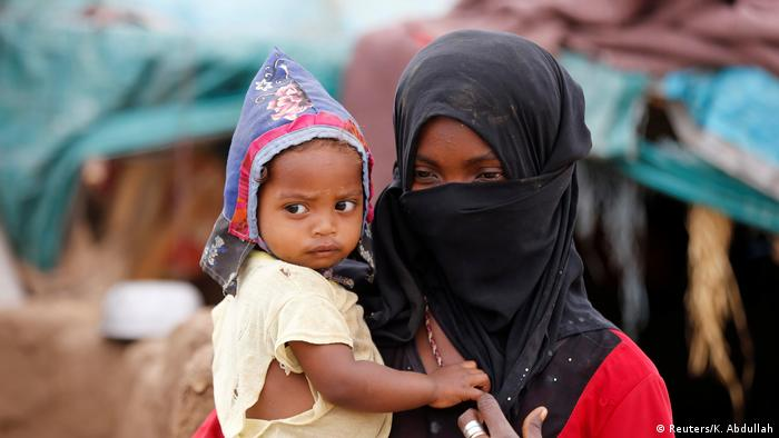 A girl carries a child near a hut in an improvised camp for internally displaced people near Abs of the northwestern province of Hajja, Yemen February 18, 2019 (Reuters/K. Abdullah)
