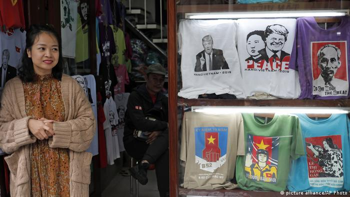 A woman stands outside her stall next to Trump and Kim T-shirts (picture alliance/AP Photo)