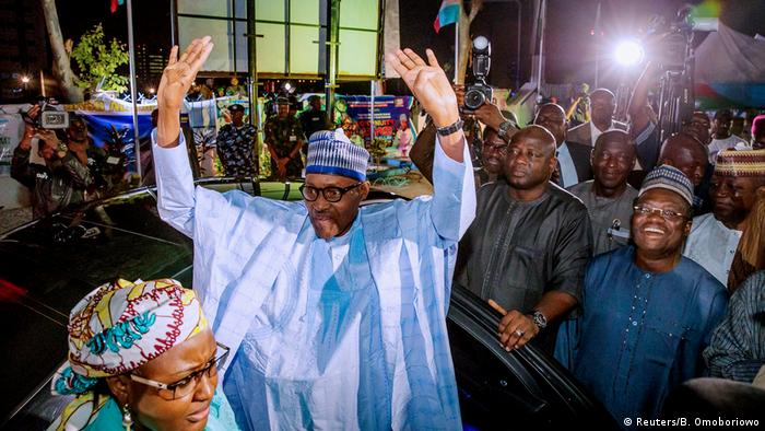 Nigerian President Muhammadu Buhari holds up his hands and greets his supporters as he steps out of a car. He is surrounded by supporters and flashing cameras
