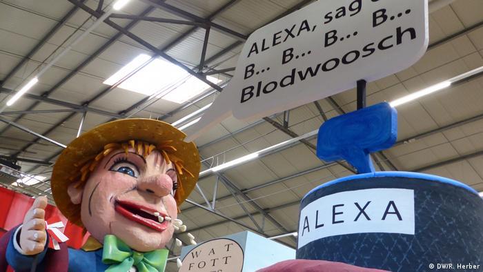 Alexa, sag Blodwoosch sagt die Figur auf dem Motivwagen für Rosenmontag. Daneben steht eine Nachbildung des sprachgesteuerten Amazon Echo mit der Aufschrift Alexa.