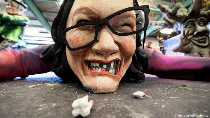 Andrea Nahles wird auf diesem Wagen des Mainzer Carneval Vereins mit herausgeschlagenen Zähnen auf dem Boden liegend dargestellt. Sie ist aus ihren roten SPD-Stöckelschuhen gekippt.