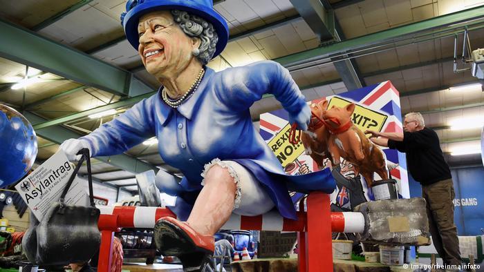 Die Queen flieht mit ihren beiden Hunden über eine Schranke vor dem Brexit-Chaos. In der Hand hält sie einen Asylantrag für Deutschland.