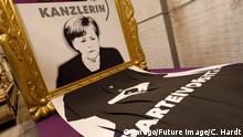 Ein Porträt Angela Merkels in einem goldenen Rahmen. Ein Großteil des Bildes hängt in Streifen geschreddert am unteren Rand heraus.