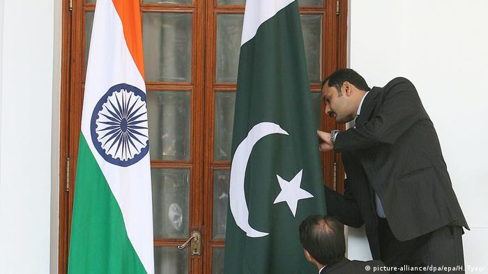 An Indian official adjusts the Pakistani flag prior to delegation levels talks at the Hyderabad House in New Delhi, India on 25 February 2010.