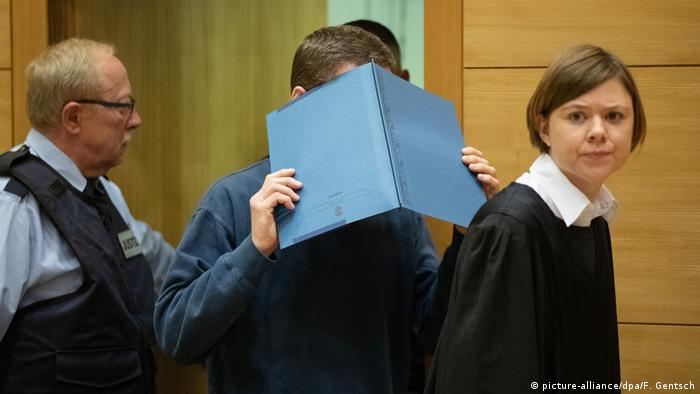 Klaus O., who poisoned his colleagues' sandwiches with lead, hides his face at this trial in Bielefeld, Germany