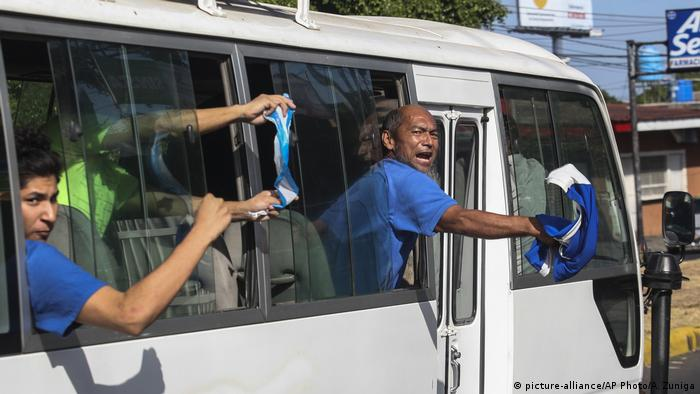 Released prisoners being driven away in minibuses wave Nicaraguan flags