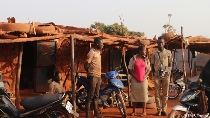 Several people stand in front of small mud-brick dwellings