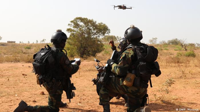 Zwei Soldaten knien auf dem Boden, über ihnen fliegt eine Drohne