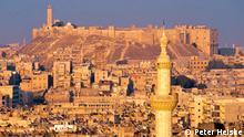 rechts der Torbau der Zitadelle. Zu dem Zeitpunkt (2001) war das Minarett der Großen Moschee gerade eingerüstet View from Khair ad-Din al-Asadi street. Between the minaret of the citadel mosque and the new minaret one can see the umayyad mosque minaret (under restoration). [Original:' <Al-Qal'a, Halab/ Aleppo, Vgl. Bild 1254 - 1277 ! - Gesehen im Abendlicht von ~ Westen, etwa von der Straße Khair ad-Dîn al-Asadi. Zwischen dem Minarett der Moschee der Qal'a und dem neueren Minarett rechts sieht man unter der Mauer das eingerüstete Minarett der Omayyaden-Moschee (vgl. Bild 1226, 1227 !). Der GPS-Tag ist approximativ !']