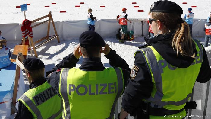 Austrian Federal Police officers stand at the finish area of a men's cross country skiing 15km classic competition, at the Nordic Ski World Championships, in Seefeld, Austria, Wednesday, Feb. 27, 2019. Austrian authorities say five elite athletes and four others have been arrested in doping raids in the country and neighboring Germany amid the Nordic skiing world championships.