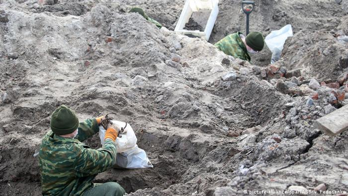Soldiers unearthing the remains with spades and gloved hands