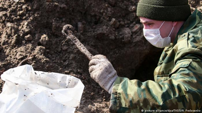 A soldier discovers part of a skeleton at the site in Brest