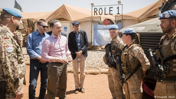 Germany's Foreign Minster Heiko Maas stands talking to German troops
