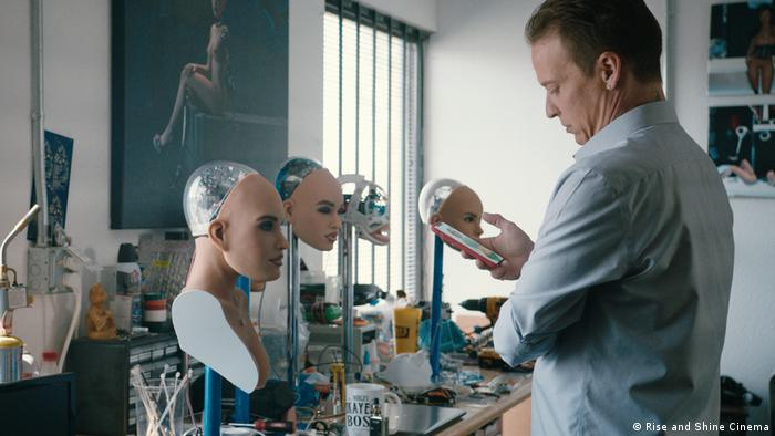 Scene from 'Hi A.I.' in which a researcher looks at data on a smartphone, in a laboratory full of robotic heads with women's faces (Rise and Shine Cinema)