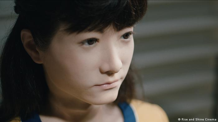 Still from 'Hi, A.I.' showing a humanoid robot face that looks almost like a real Japanese girl. (Rise and Shine Cinema)