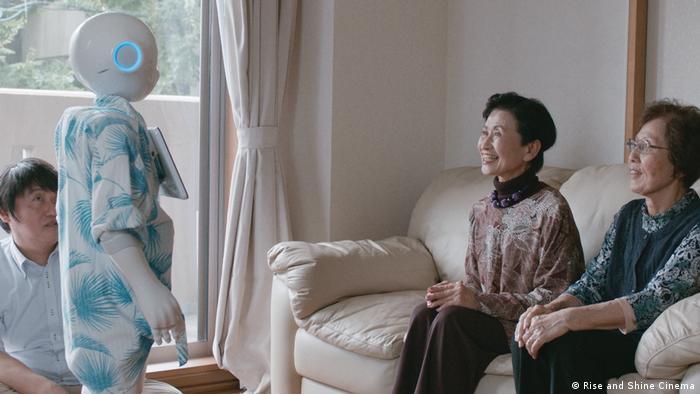 Filmstill aus Hi, AI: ein Roboter steht im Wohnzimmer, drei Frauen lächeln ihn an (Rise and Shine Cinema)