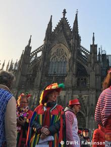 Costumed people celebrating Carnival in front of the Cologne Cathedral