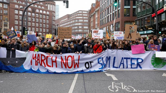 A banner reading March now or swim later held up in a protest demanding for urgent measures to combat climate change, in Hamburg, Germany, March 1, 2019