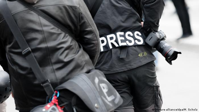 A person wearing black and carrying a camera bears the word press on their back (picture-alliance/dpa/M. Scholz)