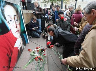 Люди кладут цветы к портрету Анны Политковской
