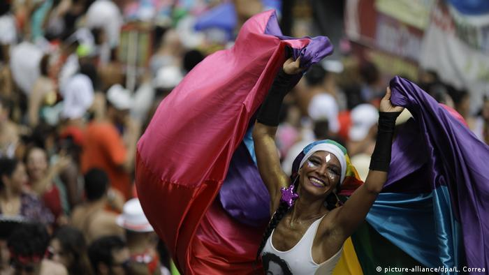 A woman wearing a rainbow cape celebrates the opening of Carnival in Rio de Janeiro, Brazil