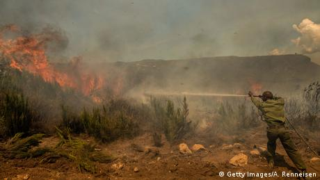 A man sprays water from a hose towards flames in scrubland on Mount Kenya