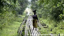 A woman walks along an oil pipeline near Shell's Utorogu flow station in Warri, Nigeria, Sunday, Jan. 15, 2006. Nigerian troops battled militia fighters in swamps around a Royal Dutch Shell oil platform that militants attacked at dawn Sunday, the third assault on Shell oil facilities in less than a week in the troubled region. Shell confirmed the attack on the Benisede oil platform in the southern oil-rich Niger Delta and said some of its staff had been injured and taken to hospital. The company also said it had begun evacuating personnel from vulnerable facilities in the region because of worsening security. (AP Photo/George Osodi) |