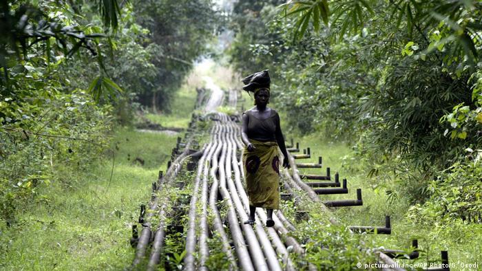 A woman walks along an oil pipeline in Nigeria