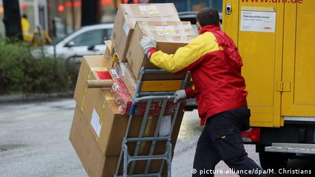 A courier from German postal service DHL delivering an assortment of big and small packages mounted on a push cart