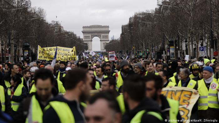 Yellow vest protests in Paris: Masses of people wearing yellow vests in the streets of Paris in front of the Arc de Triomphe.