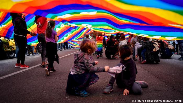 Crianças brincam embaixo de uma grande bandeira do movimento LGBT durante a marcha