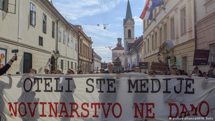 Croatian journalists march holding a banner that reads: 'You took over media, we won't give up journalism'