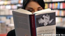 Eine junge Frau blättert am Donnerstag (08.10.2009) bei Buchhabel in Wiesbaden in Herta Müllers Roman Atemschaukel, der für den Deutschen Buchpreis 2009 nominiert ist. Der Nobelpreis für Literatur geht in diesem Jahr an die deutsche Schriftstellerin Herta Müller. Die 56 Jahre alte Autorin zeichne mittels Verdichtung der Poesie und Sachlichkeit der Prosa Landschaften der Heimatlosigkeit, erklärte die Akademie. Herta Müller ist in Rumänien geboren und verarbeitet in ihren Werke ihre Erlebnisse von Fremdheit und politischer Verfolgung. Müller ist die zwölfte Frau mit dem Literatur-Nobelpreis. Mit ihr wurde zum 13. Mal ein Vertreter der deutschsprachigen Literatur gewürdigt. Der Nobelpreis wird am 10. Dezember in Stockholm vergeben. Foto: Arne Dedert dpa +++(c) dpa - Report+++