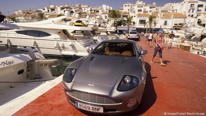 A Porsche sports car parking in front of a yacht in the Puerto Banus marina of Marbella