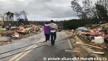 People walk amid debris in Lee County, Ala., after what appeared to be a tornado struck in the area Sunday, March 3, 2019. Severe storms destroyed mobile homes, snapped trees and left a trail of destruction amid weather warnings extending into Georgia, Florida and South Carolina, authorities said. (WKRG-TV via AP) |