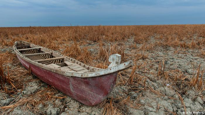 A traditional canoe-like boat sits on the dry and cracked marshland (photo: John Wreford)