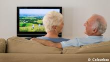 A senior couple watching tv and talking