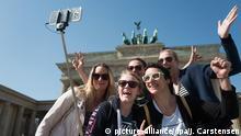 08.04.2018, Berlin: Bei strahlendem Sonnenschein machen fünf Touristinnen aus Kassel an ihrem letzten Urlaubstag in Berlin ein Selfie vor dem Brandenburger Tor. Foto: Jörg Carstensen/dpa   Verwendung weltweit