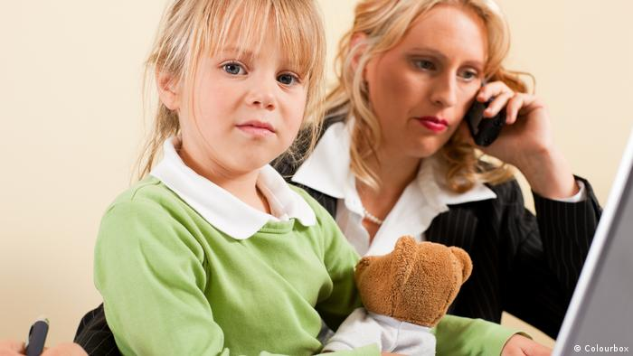 A woman speaks on the phone in a business suit while sitting with a young girl who is holding a teddy bear (Colourbox)